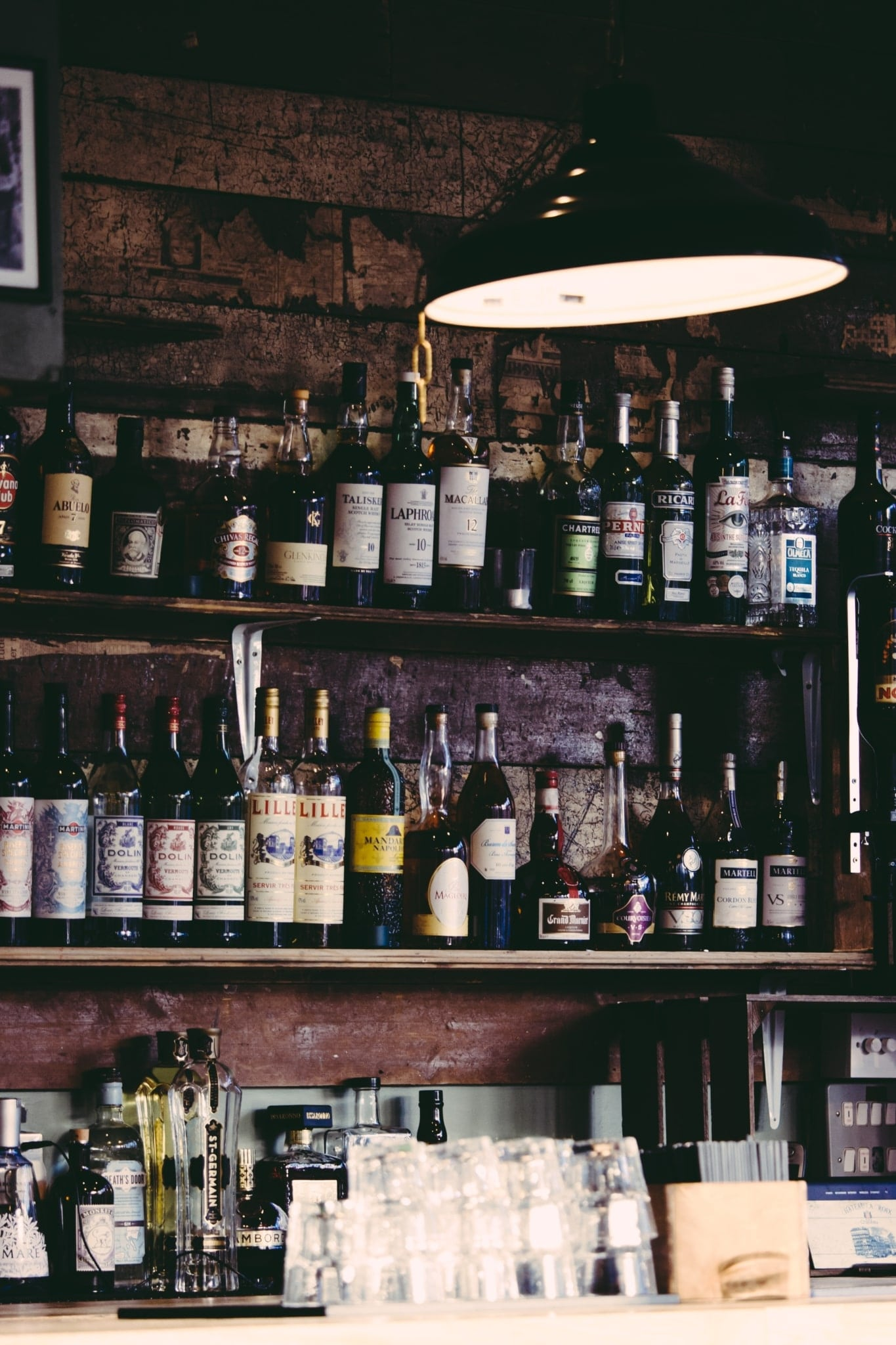 Photo of a bar with shelves with liquor